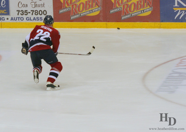 Hockey player chases the puck on ice.