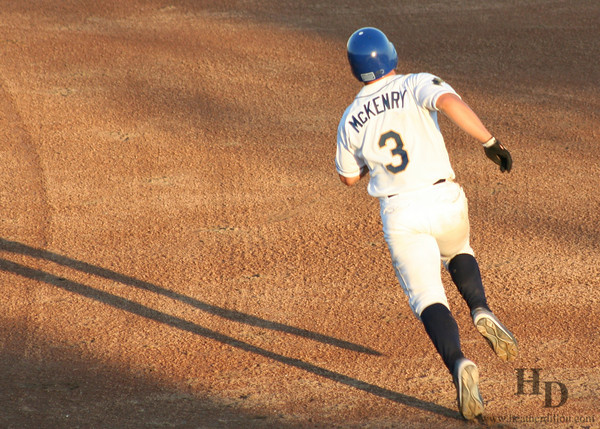 Runner heads to the next base late in the evening during a dust devil game.