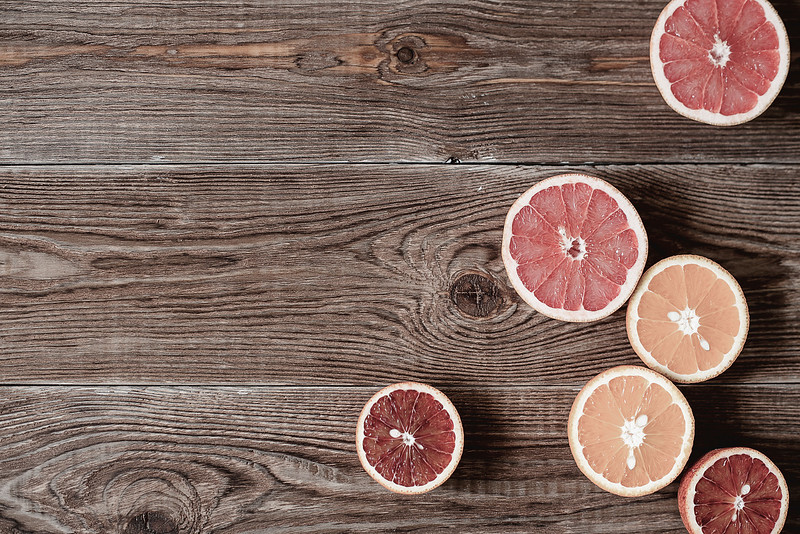 Citrus fruits cut in half. Oranges, bloody oranges, grapefruits on wood table background with copy space. Top view