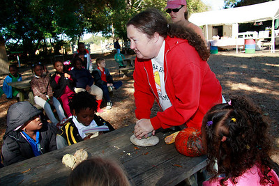Linda Legare using stones to show the kids how the settlers grinded corn to make meal..