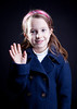 A cute little girl in a dark pea coat waving.