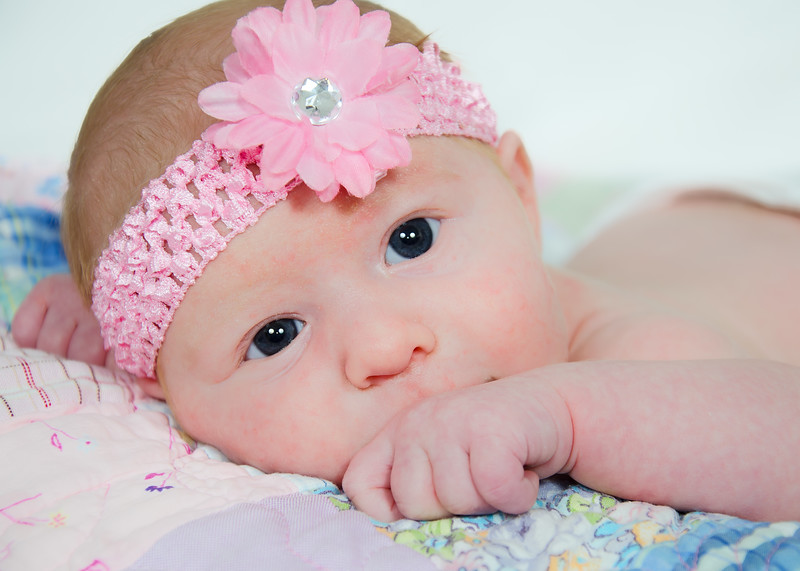 Newborn Photo with pink bow looking