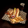 Monster club sandwich on a basket with fries and a cool beer