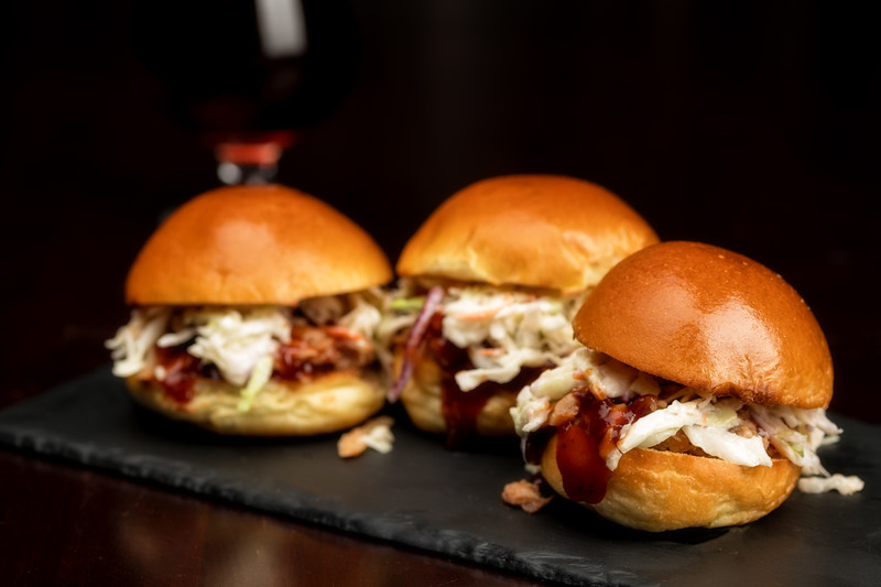 Three small pulled pork sliders side by side