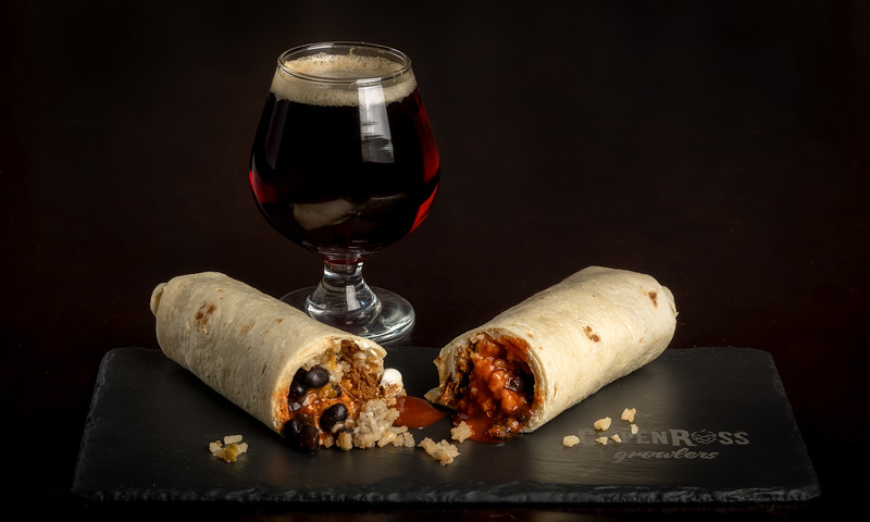 Burrito cut in half with a beer