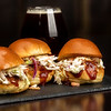 Close up of triple sliders and a beer
