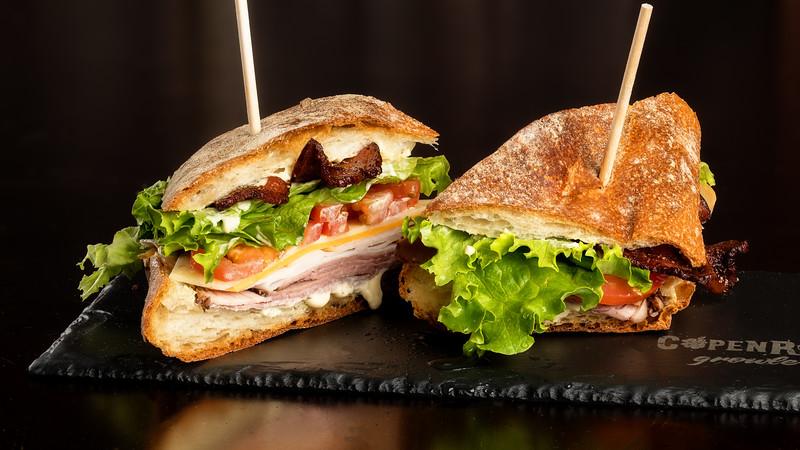 Club sandiwch halfs on a slate plate
