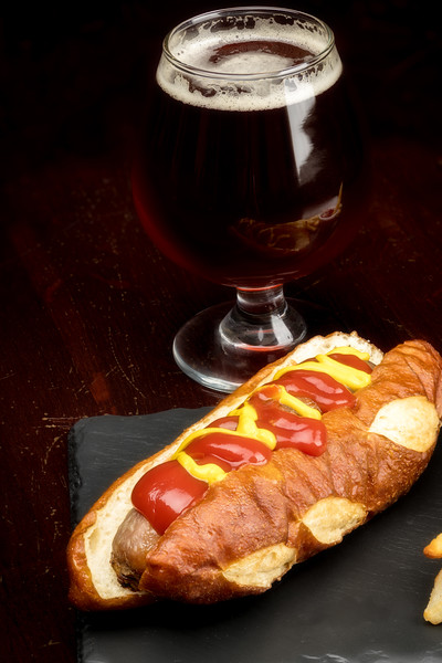 Close up of a Polish Hotdog with a refreshing glass of beer in a fancy glass
