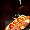 Ketchup and mustered added to a dog in a pretzel bun with a beer