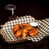 Several Chicken Wings in a basket with a glass of beer