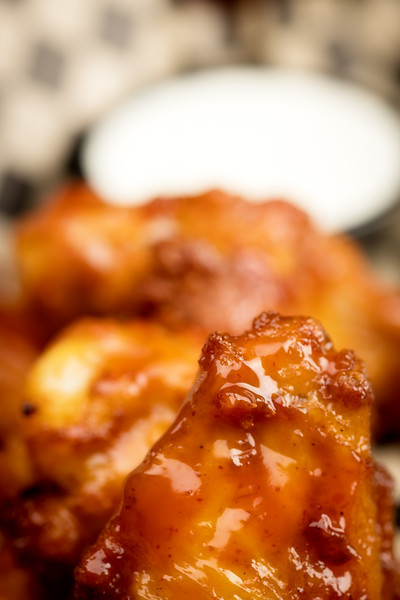 Macro close up of a chicken wing with glistening glaze and dipping sauce