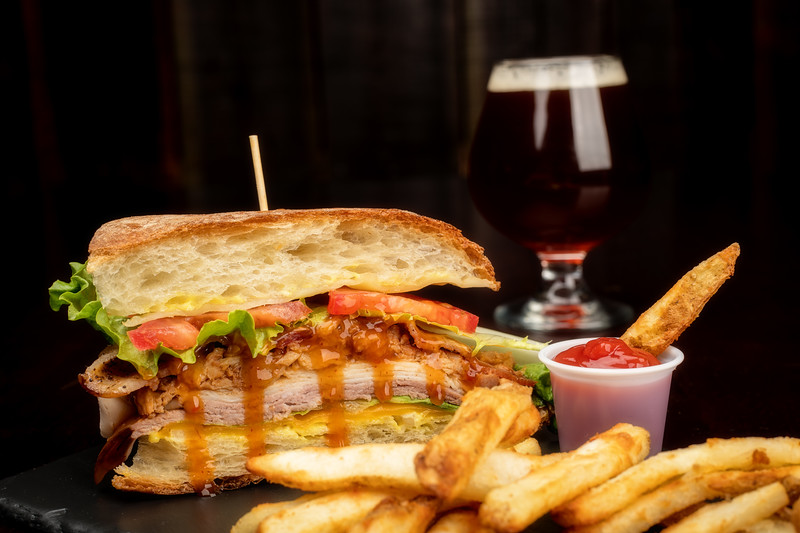 Close up of a restaurant monster sandwich with French fries and a beer