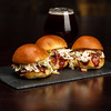 Triple sliders made of puller pork and a beer on a slat plate