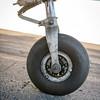 Closeup of an airplane wheel on the black tarmac