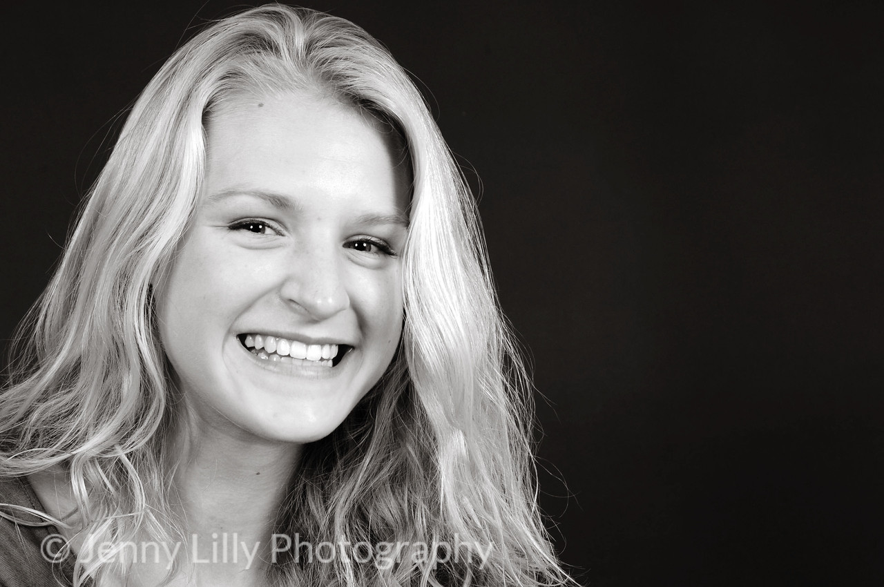pretty blonde teenage girl, smiling, isolated on dark background