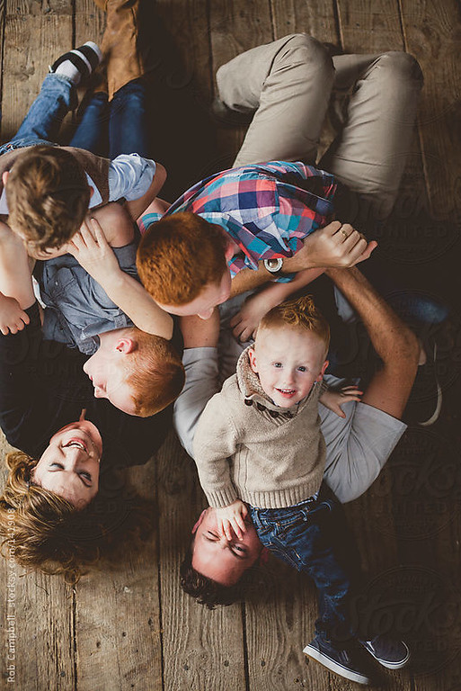 Family having fun tickling on old wood floor