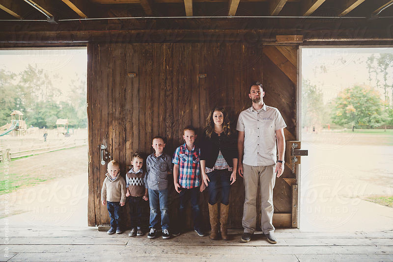 Family of six posing for serious mug shot on barn door