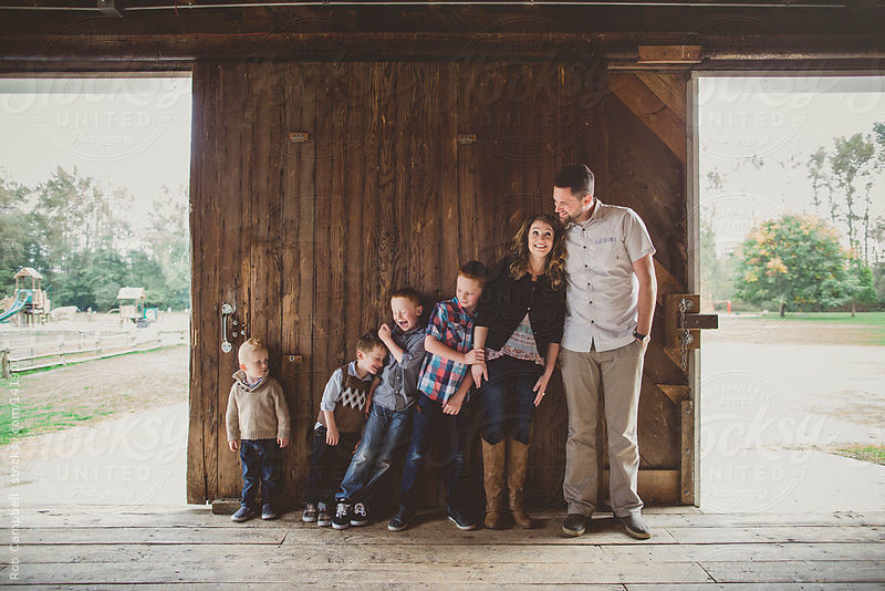 Family of six leaning on each other on wood door