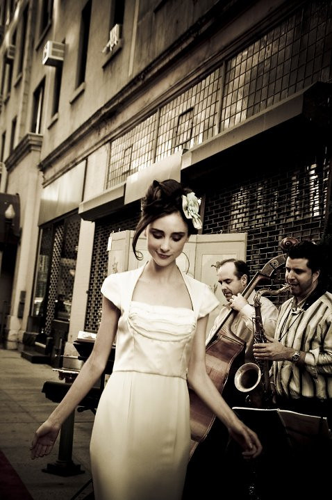 Woman walking by musicians, New York, NY, 2010.