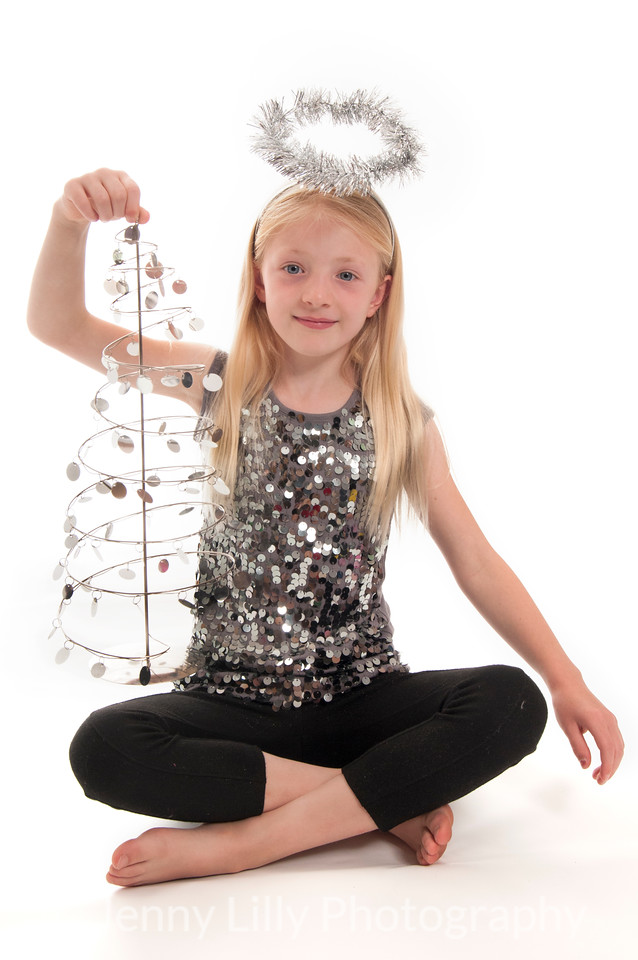 pretty blonde girl with a tinsel halo, and a Christmas tree, isolated on white background