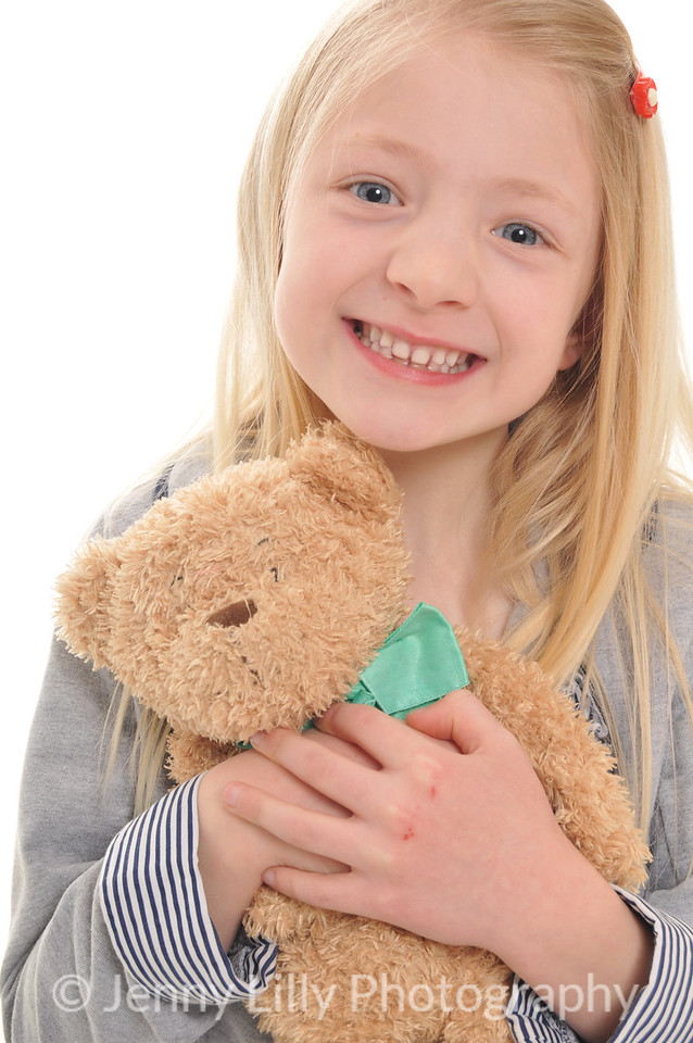 pretty blonde girl cuddling her teddy bear isolated on white background