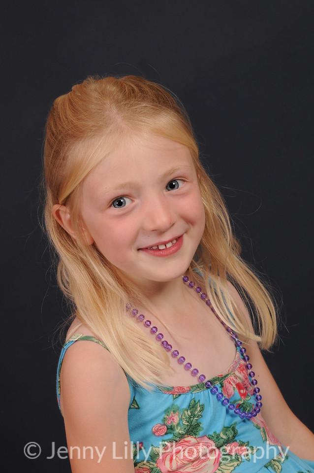 pretty blonde child in sundress isolated on dark background