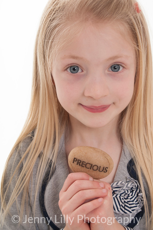pretty blonde girl holding engraved message stone, isolated on white background