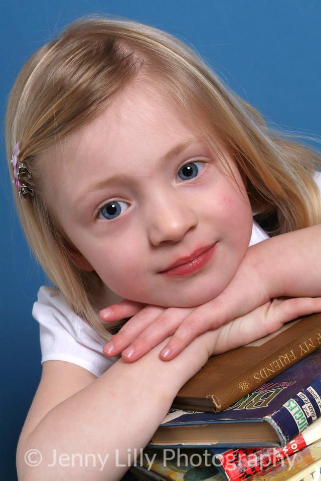 pretty blonde girl in school uniform isolated on dark background