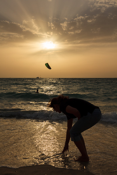 Silhouette of a woman touching water in kite beach.