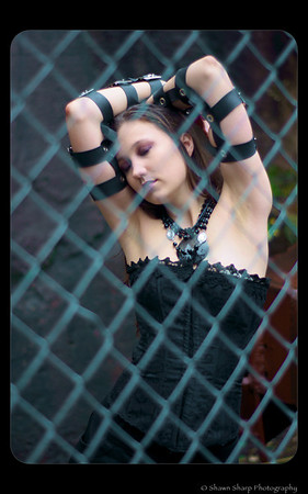 Looking sombre behind a fence wither her arms raised over her head. To me this one really shows off her black corset, and the arm bands are a nice touch...