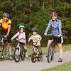Greg Sousa and his wife Sara and their children Belle and Abe ride bikes in Durham. Sousa survived brain cancer last year.