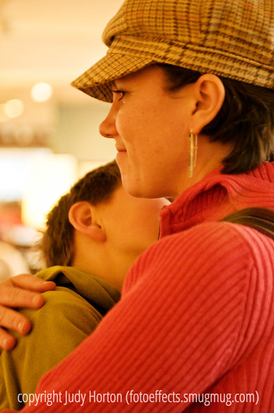A mother and her son enjoy a quick hug while shopping.