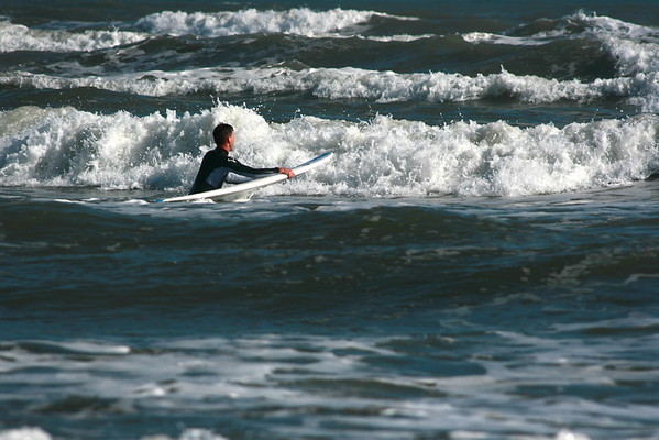 a surfer heads into the waves of the Gulf of Mexico in Galveston in February