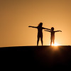 Silhouette shot of two kids while posing and holding their hands on top of a sand dune with sun visible