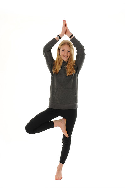 pretty blonde teenage girl standing on one foot in a yoga pose, isolated on white background