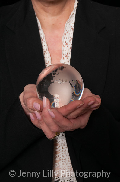Vintage 1940's style woman  holding a glass globe, isolated on black background