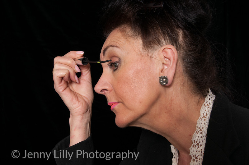 Vintage 1940's style womanapplying her make up isolated on black background