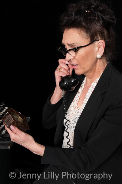 Vintage 1940's style woman in office situation, worried about the time, and angry on the telephone, isolated on black background