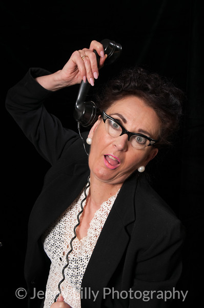 Vintage 1940's style woman in office situation,strangling herself with the telephone cord, isolated on black background
