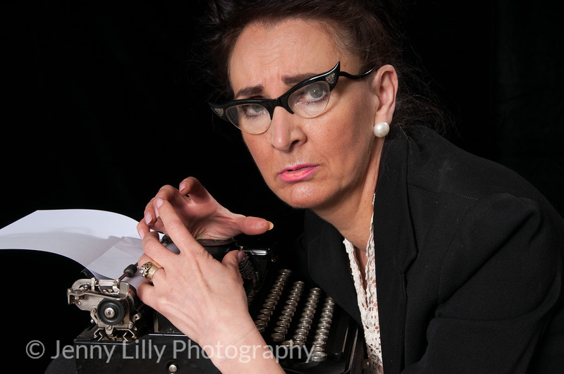 Vintage 1940's style woman in office situation, struggling with her typewriter, isolated on black background