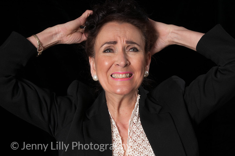 Vintage 1940's style woman in office situation, tearing her hair out, isolated on black background