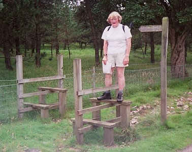 11 - Stile Goddess! A redundant stile which I insisted on using somewhere between Appleby and Shap in August 2002. At this time I was down to the lowest fighting weight I ever had, and I have been expanding ever since. A rare view of my legs, normally hidden beneath an ankle length skirt or jeans.