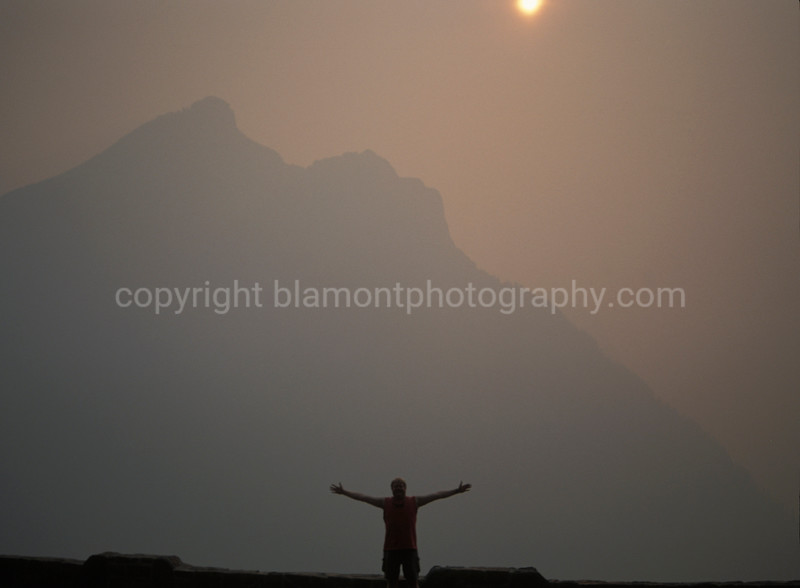 "My 1st self portrait on my 1st trip to Glacier Nat. Prk. (Crown of the Continent). I set up my tripod and hit the timer shot on my 1st. drive on Going To The Sun Road... The fires where very bad the summer of 2003 in MT.  As they are now in 2012... Exsqueeze me while I kiss the sky... In whatever you do, remember to give it a ""KISS""... And keep it simple stupid ^-)<br />       The distinct and pungent smoke of burning pine sap filled the lungs and the renta car interior. I now have an inate respect for the Smoke Jumpers, and all the Fire Fighters who risk thier lives and partake in this yearly Summer ritual when the Wild Fires rage. Seeing Glacier like this was burned into my memory...No pun intended &-)"