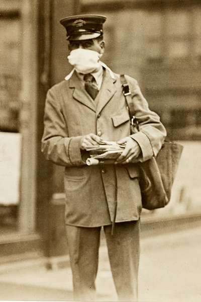 A New York City letter carrier wears a mask while delivering mail in October 1918. Image: National Archives