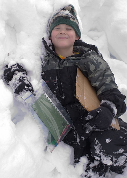 My son Erik relaxes in a snowbank on school grounds.
