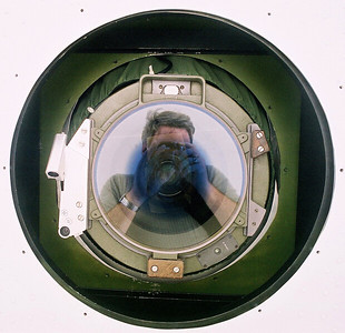 Self portrait: I took this photo of my reflection as I laid on my back under the belly of an aerial mapping plane.  My refection is in the lens of the aerial mapping camera that is built into the belly of this aircraft.