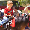 """RUSSELL L. FRAYRE<br /> 91111<br /> A very popular attraction were the pony rides at the Marstons Mills Village Day.  Here Jordan Munoz, age 4 of Hyannis takes """"Sunny"""" for a ride."""