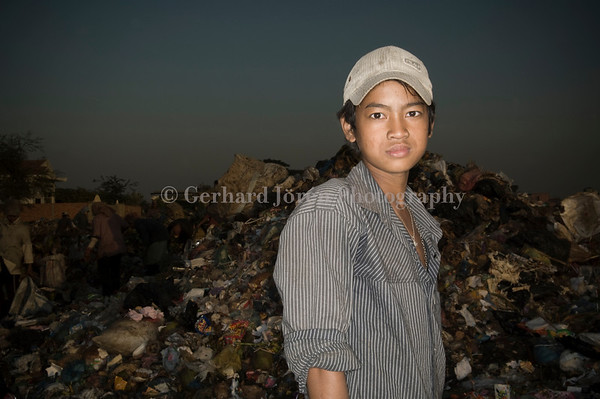Kouk Seaha, 17 years old. He works full time at the dump and makes USD 1 a day. He wish he could study and become a teacher. He has been working here for 2 years and found all his cloths at the dump.<br /> Stung Meanchey Municipal Waste Dump  in southern Phnom Penh, in  Stung Meanchey district. Over 500 children works long hours side by side with some 1500 adults.  They all live in the slums surrounding the dump, which covers about 100 acres, or almost 6 hectares. They make less then US$ 1,50 a day