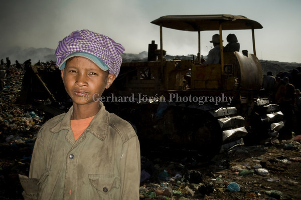 Srous Sray Toun, 14 years old, would like to study, but have to help his family to earn money at the dump. He has found all his cloths at the dump.<br /> Stung Meanchey Municipal Waste Dump in southern Phnom Penh, in Stung Meanchey district. Over 500 children works long hours side by side with some 1500 adults. They all live in the slums surrounding the dump, which covers about 100 acres, or almost 6 hectares. They make less then US$ 1,50 a day
