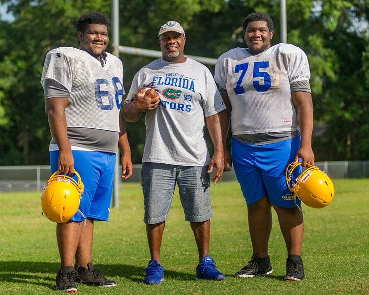 John L. Williams and his fifteen-year-old twins Javon (68) and John (75) who are in their first year of playing for Palatka.
